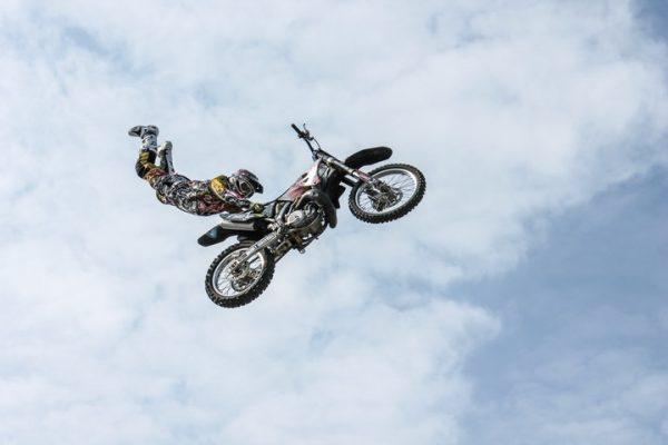 Hoppande motorcykel med förare hängande